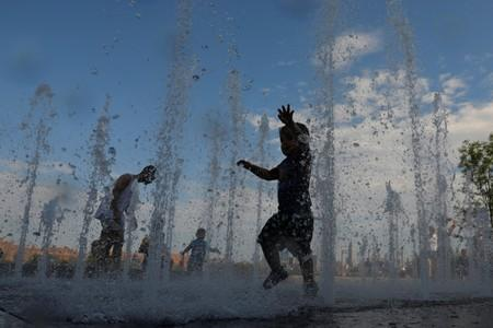 Children play in a water feature in Domino Park as a heatwave continued to affect the region in Brooklyn, New York City