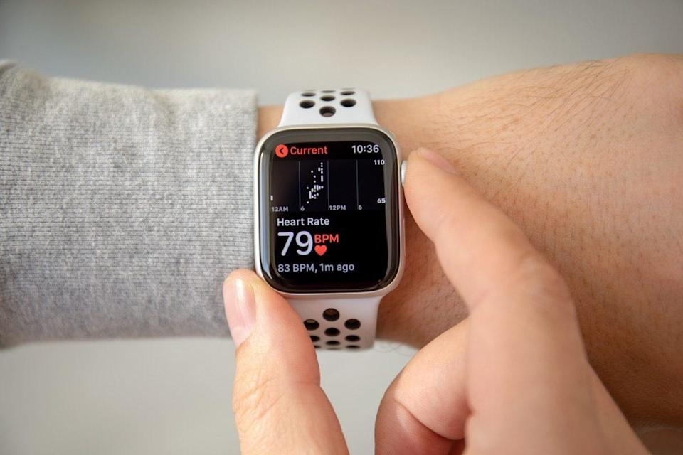 an hand with Apple Watch Series 4 with Heart Rate on the screen. Apple Watch was created and developed by the Apple inc