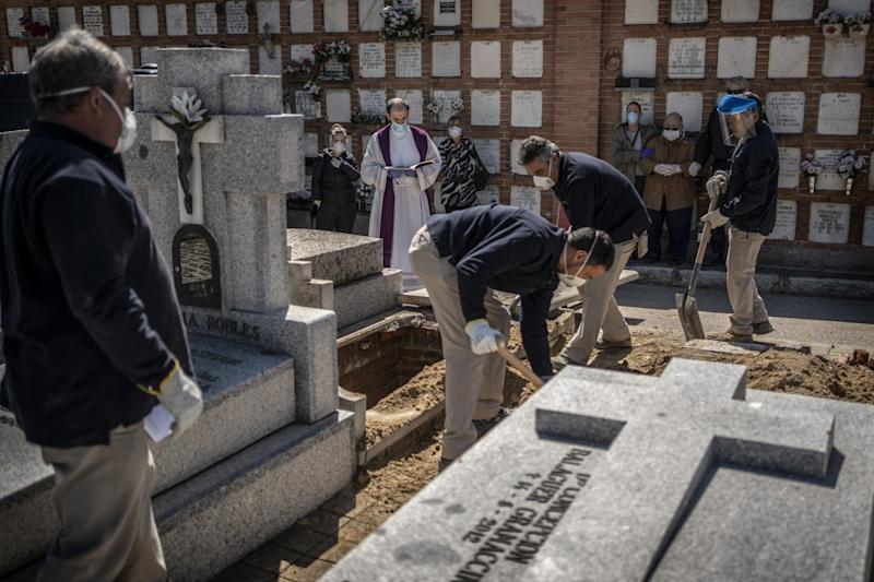 SPAIN: A priest and relatives pray as a COVID-19 victim's coffin is buried at the Almudena cemetery in Madrid.