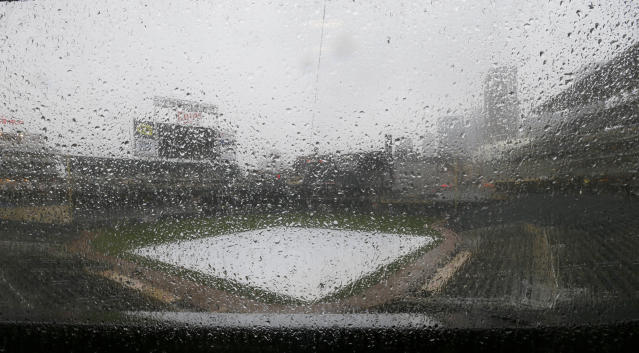 Rain falls on the tarp-covered field as the Minnesota Twins baseball game against the Detroit Tigers in Minneapolis, Sunday, April 27, 2014, is postponed due to the weather. (AP Photo/Ann Heisenfelt)