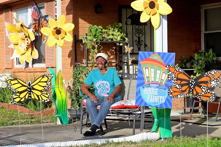 Yvonne Milton sits in front of her New Orleans home surrounded by the bee and flower creations of artists Re Howse and Bill Tucker.