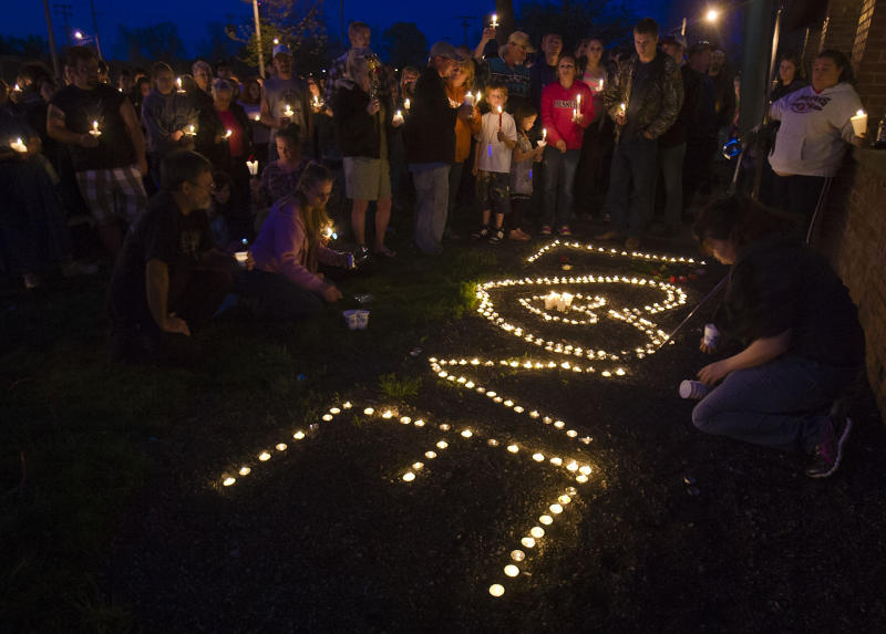 """People stand near candles that spell out """"love""""  during a prayer vigil for Lana-Leigh Bailey and the other victims at Forest Park Friday, May 10, 2013 in Ottawa, Kan.  Kyle Flack, a 27-year-old convicted felon was charged Friday in the deaths of a woman and two men whose bodies were found at an eastern Kansas farm home earlier this week, according to a criminal complaint. (AP Photo/The Kansas City Star, Allison Long)"""