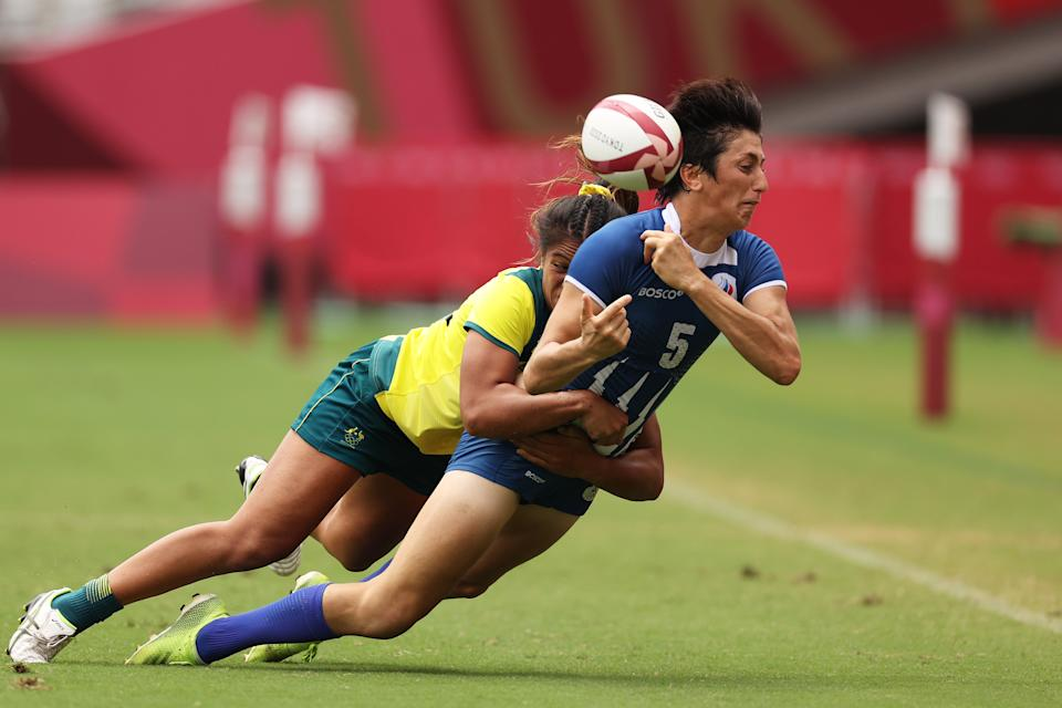<p>Baizat Khamidova of Team ROC offloads the ball in a tackle from Sariah Paki of Team Australia in the Women's Placing 5-8 match between Team ROC and Team Australia during the Rugby Sevens on day eight of the Tokyo 2020 Olympic Games at Tokyo Stadium on July 31, 2021 in Chofu, Tokyo, Japan. (Photo by Dan Mullan/Getty Images)</p>