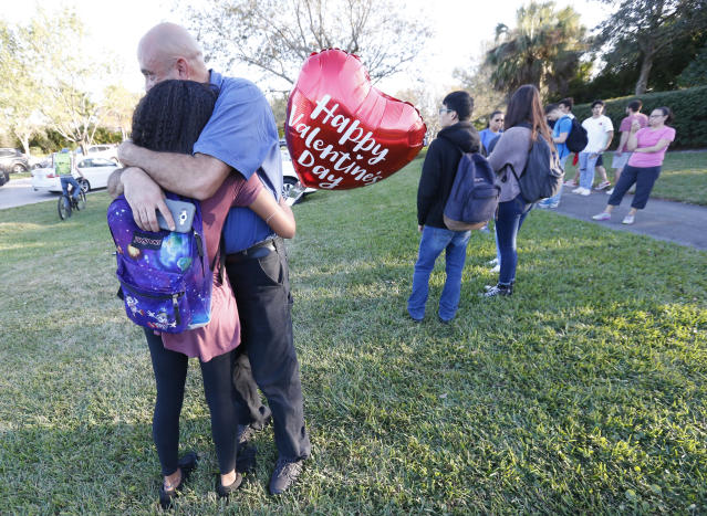 <p>Family member embrace following a shooting at Marjory Stoneman Douglas High School, Feb. 14, 2018, in Parkland, Fla. (Photo: Wilfredo Lee/AP) </p>
