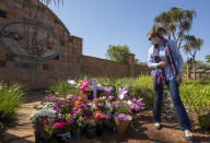 Christine Wright leaves flowers outside the complex where the Dickason family lived prior to their emigration to New Zealand, in Pretoria, South Africa, Thursday, Sept. 23, 2021. People in the town of Timaru are planning an evening vigil outside the home of three young girls who were killed last week in a crime that shocked New Zealand. The girls' mother Lauren Dickason has been charged with their murder. (AP Photo/Themba Hadebe)