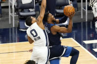Minnesota Timberwolves' Malik Beasley, right, drives to the basket as Memphis Grizzlies' De'Anthony Melton defends in the second half of an NBA basketball game, Wednesday, Jan. 13, 2021, in Minneapolis. The Grizzlies won 118-107. Beasley led the Timberwolves with 28 points. (AP Photo/Jim Mone)