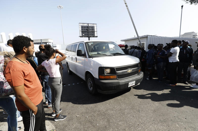 A van carrying migrants on their way to apply for asylum in the United States passes a group of migrants still awaiting a chance to apply on the border Tuesday, July 16, 2019, in Tijuana, Mexico. Nearly two dozen immigrants were allowed to cross the U.S.-Mexico border to seek asylum on Tuesday, the day the Trump administration planned to launch a drastic policy change designed to end asylum protections for most migrants who travel through another country to reach the United States. (AP Photo/Gregory Bull)