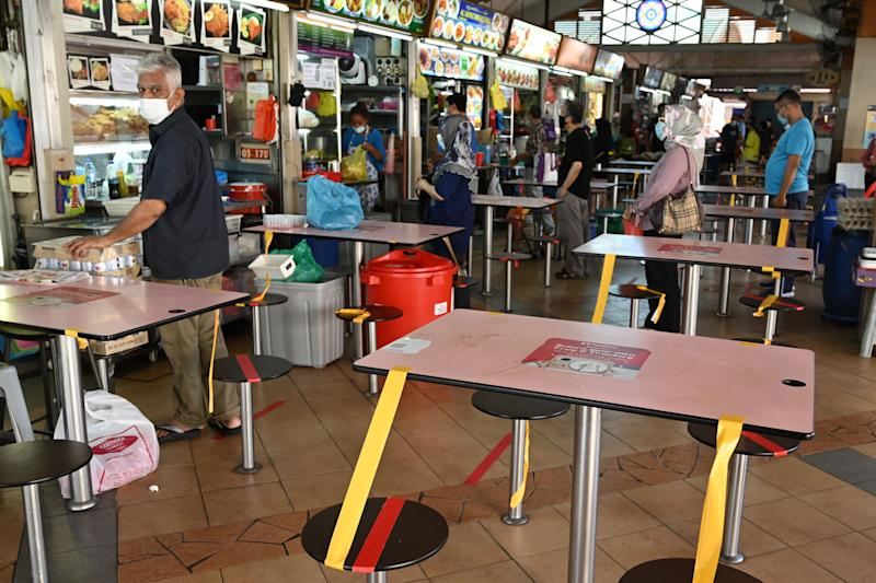 People wearing facemasks as a prevention measure against the spread of the COVID-19 coronavirus queue to buy takeaway food next to empty tables at a hawker centre in Singapore on April 22, 2020. (Photo by ROSLAN RAHMAN / AFP) (Photo by ROSLAN RAHMAN/AFP via Getty Images)