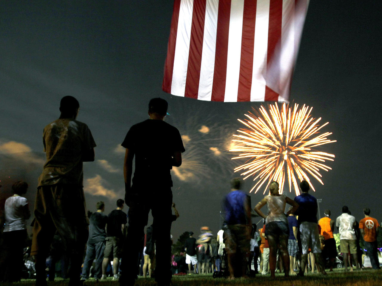 Spectators watch fireworks streak across the sky during the Fanfare and Fireworks celebration at the University of Florida on Tuesday, July 3, 2012, in Gainesville, Fla. (AP Photo/The Gainesville Sun, Matt Stamey)
