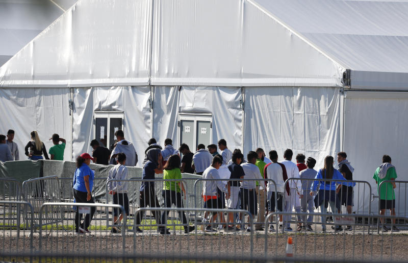 FILE- In this Feb. 19, 2019 file photo, children line up to enter a tent at the Homestead Temporary Shelter for Unaccompanied Children in Homestead, Fla.  Migrant children who were separated from their parents at the U.S.-Mexico border last year suffered post-traumatic stress and other serious mental health problems, according to an internal watchdog report obtained by The Associated Press Wednesday. The chaotic reunification process only added to their trauma.  (AP Photo/Wilfredo Lee, File)