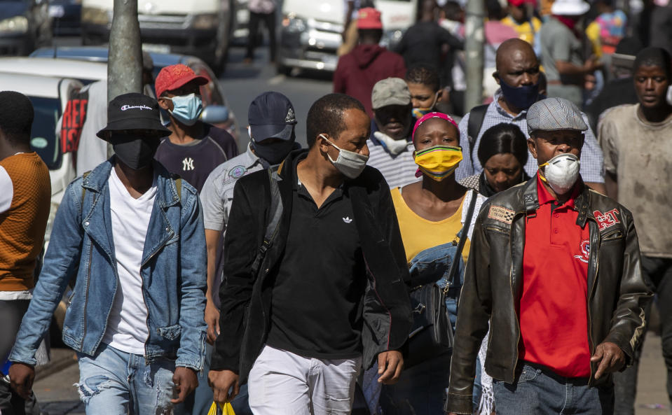 People wearing face masks to protect against coronavirus, walk on the street in downtown Johannesburg, South Africa, Monday, May 11, 2020. (AP Photo/Themba Hadebe)