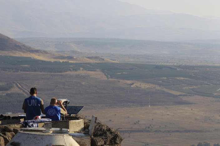 In this photo taken, Tuesday, July 24, 2012, UN soldiers observe from an old army post from the 1967 war at Mt. Bental in the Golan Heights overlooking Syria. (AP Photo/Tsafrir Abayov)