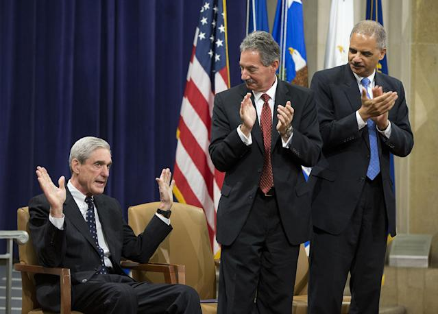 <p>Attorney General Eric Holder, right, and Deputy Attorney General James Cole, center, applaud outgoing FBI Director Robert Mueller during a farewell ceremony at the Justice Department in Washington, Thursday, Aug. 1, 2013. Mueller is stepping down in September after 12 years heading the agency (Photo: Evan Vucci/AP) </p>