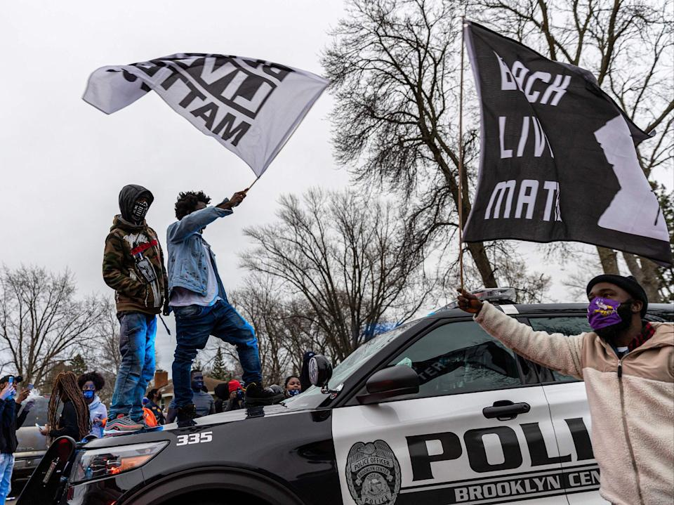 <p>Protesters stand on top of a police car as they clash after an officer reportedly shot and killed a black man in Brooklyn Center, Minneapolis, Minnesota on April 11,2021. - Daunte Wright, 20, was shot a Brooklyn Center police officer  during a routine traffic stop in Plymouth on April 11, 2021. The incident involved a multi-car crash just prior to the officer discharging their weapon, US media reports. (Photo by Kerem Yucel / AFP) (Photo by KEREM YUCEL/AFP via Getty Images)</p> (AFP via Getty Images)