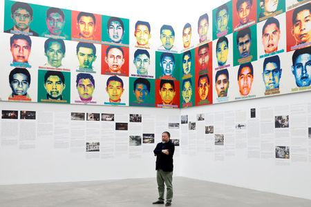 """Chinese artist Ai Weiwei poses for photographers in front of portraits of the 43 missing Ayotzinapa College Raul Isidro Burgos students during a photocall for his exhibition """"Restablecer Memorias"""", displayed at the University Museum of Contemporary Art (MUAC) in Mexico City, Mexico, April 11, 2019. REUTERS/Edgard Garrido/Files"""