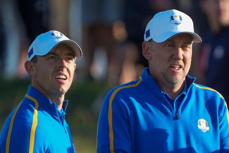 Rory McIlroy and Ian Poulter look over a shot on the second hole during their foursomes match at the Ryder Cup (Charlie Neibergall/AP) (AP)