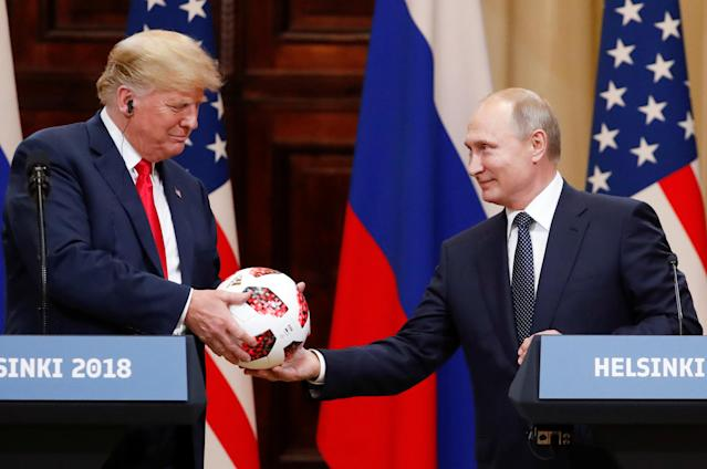 U.S. President Donald Trump receives a football from Russian President Vladimir Putin as they hold a joint news conference after their meeting in Helsinki, Finland July 16, 2018. (Photo: REUTERS/Grigory Dukor)