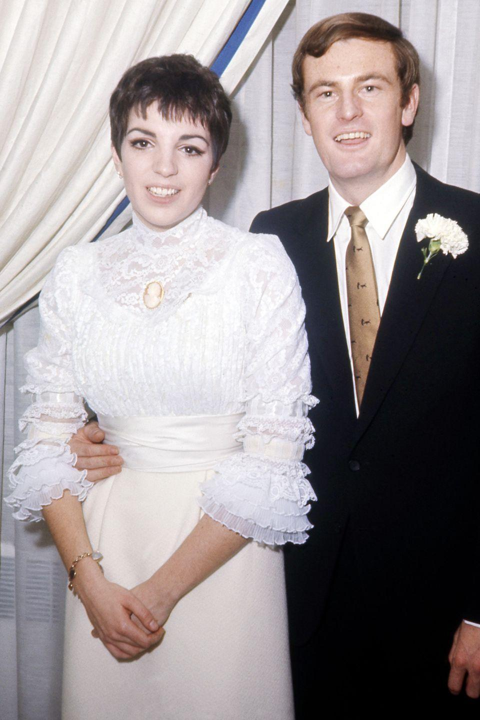 <p>For her first wedding to Peter Allen, Liza Minnelli wore all a white dress ensemble, but with her own flair. The lace blouse with ruffled sleeves and a turtleneck, paired with a sleek cream skirt, was ahead of its time.</p>
