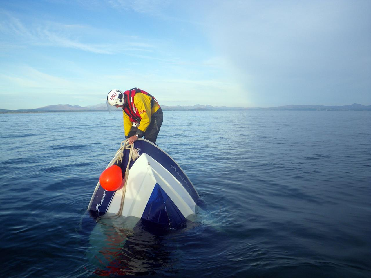 Second place photo by Paul Collins show a RNLI volunteer on an upturned boat in Abersoch, Wales (Paul Collins/Rex Features)