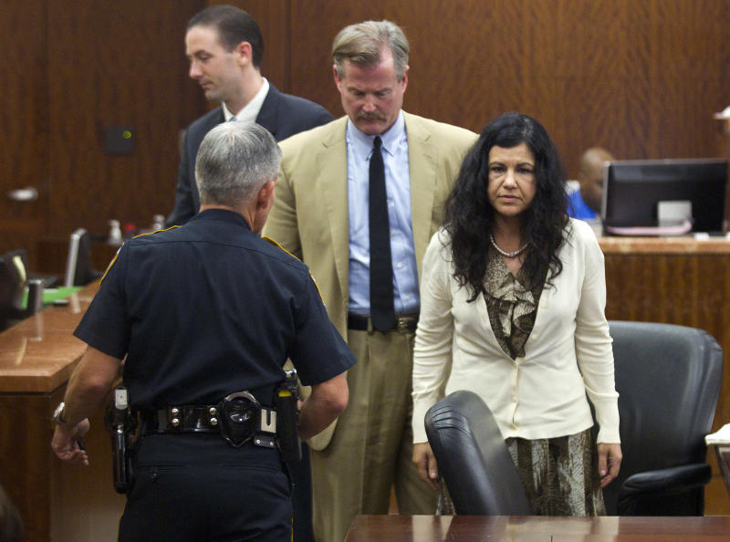 Ana Trujillo, right, stands just before being taken from the courtroom and into custody, after being found guilty of murder, on Tuesday, April 8, 2014, in Houston. Trujillo, 45, was found guilty of fatally stabbing her boyfriend with the stiletto heel of her shoe, hitting him at least 25 times in the face. (AP Photo/Houston Chronicle, Brett Coomer)