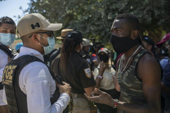 A uniformed Mexican police officer talks with a Haitian migrant wearing a mask.
