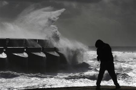 A man watches stormy seas in strong winds as waves crash on the harbour wall at Brighton marina in south east England October 28, 2013. REUTERS/Luke MacGregor