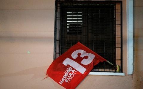 A flag of Fernando Haddad, presidential candidate of Brazil's leftist Worker Party (PT), is seen in a window, in Fortaleza - Credit: Reuters