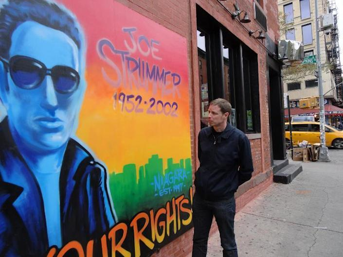 Nick Hall, a Spanish-based British filmmaker, poses next to a mural of late Clash singer and guitarist Joe Strummer in New York City on October 10, 2014 (AFP Photo/Shaun Tandon)