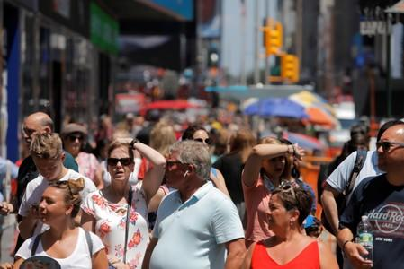 People react while walking through Times Square as a heatwave continues to affect the region in New York