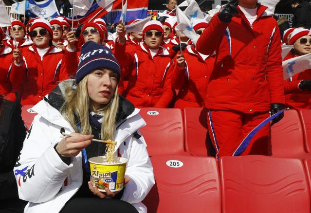 Alpine Skiing - Pyeongchang 2018 Winter Olympics - Men's Giant Slalom - Yongpyong Alpine Centre - Pyeongchang, South Korea - February 18, 2018 - An unidentified athlete eats noodles in front of North Korean cheerleaders. REUTERS/Kai Pfaffenbach