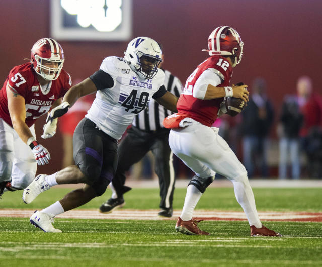 Northwestern defensive lineman Adebawore Adetomiwa (49) closes in on Indiana quarterback Peyton Ramsey (12) during the second half of an NCAA college football game, Saturday, Nov. 2, 2019, in Bloomington, Ind. Indiana won 34-3. (AP Photo/Doug McSchooler)