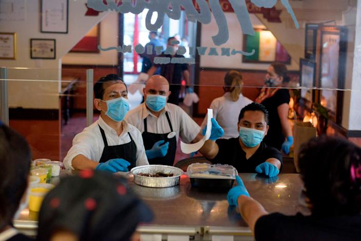 Servers at The Original Ninfa's wear gloves and masks while fulfilling takeout orders from the kitchen amid the pandemic in Houston, Texas, on May 1, 2020.