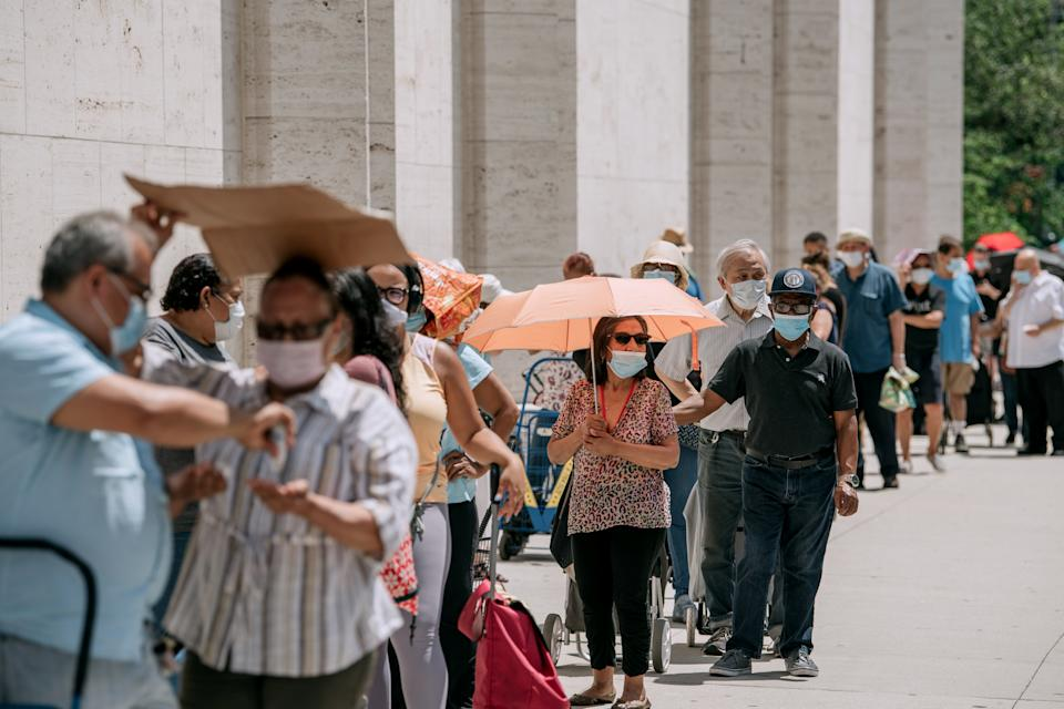 New Yorkers in need wait in a long line to receive free produce, dry goods, and meat at a Food Bank For New York City distribution event at Lincoln Center on July 29, 2020 in New York City. (Photo by Scott Heins/Getty Images)
