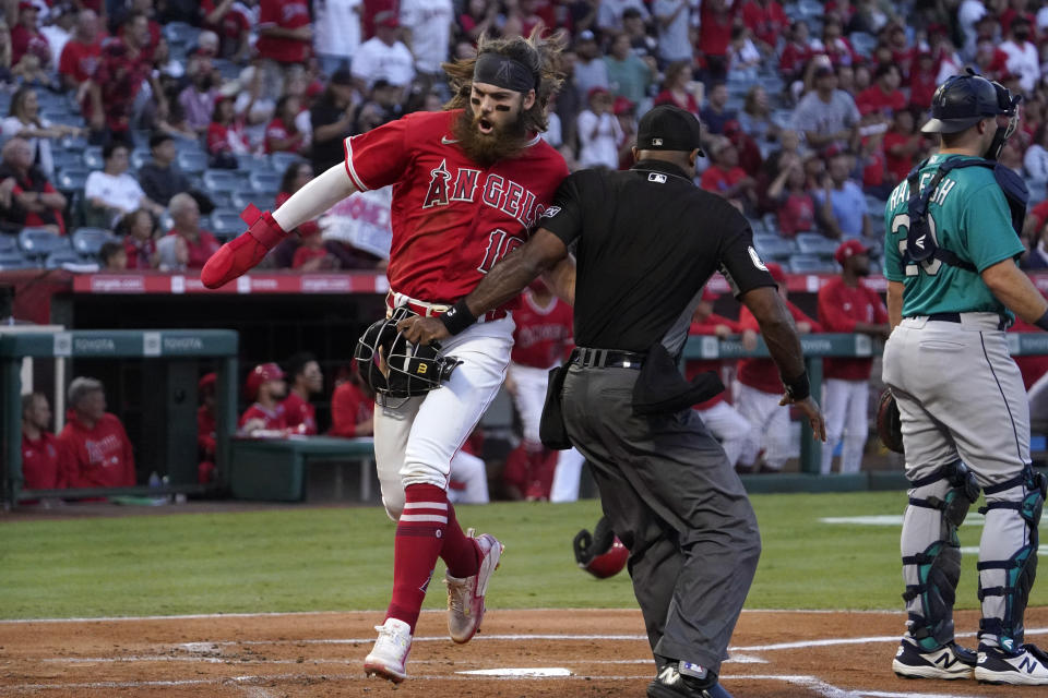 Los Angeles Angels' Brandon Marsh, left, collides with home plate umpire Alan Porter, center, as he scores on a triple by Shohei Ohtani while Seattle Mariners catcher Cal Raleigh stands at the plate during the first inning of a baseball game Saturday, Sept. 25, 2021, in Anaheim, Calif. (AP Photo/Mark J. Terrill)