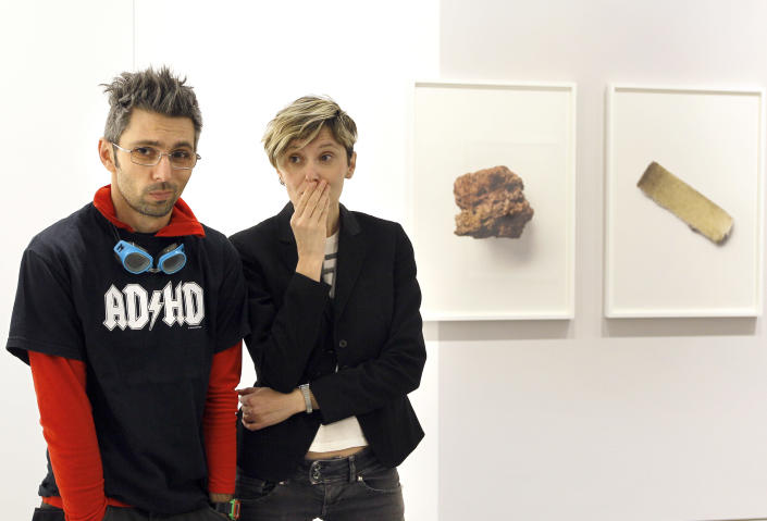 Artists Eva, right, and Franco Mattes in front of photographs of fragments from art work called 'Stolen Pieces' on display at the Carroll/Fletcher Gallery in London, Thursday, April 12, 2012. The exhibition opens to the public on April 13, and displays stolen fragments from works by a roll call of the 20th century's best known artists. (AP Photo/Kirsty Wigglesworth)