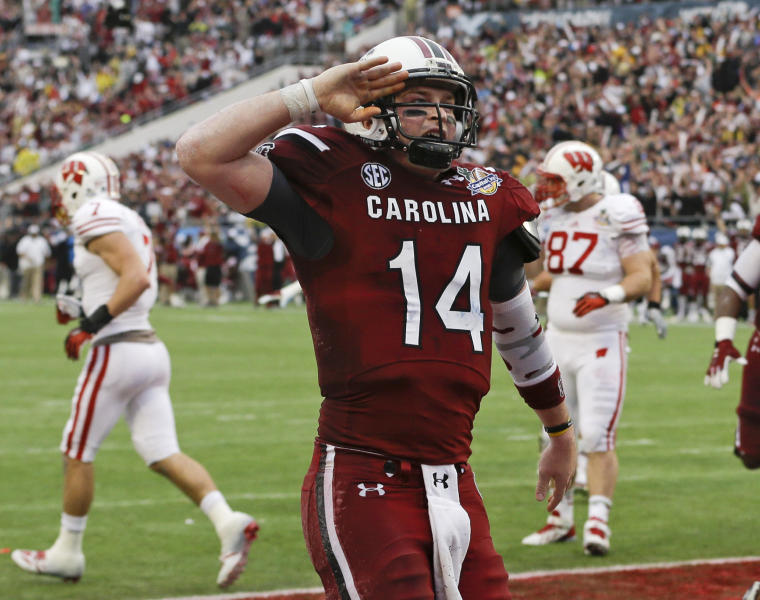 South Carolina quarterback Connor Shaw (14) salutes towards fans after catching a touchdown on a pass from receiver Bruce Ellington during the first half of the Capital One Bowl NCAA college football game against Wisconsin in Orlando, Fla., Wednesday, Jan. 1, 2014.(AP Photo/John Raoux)