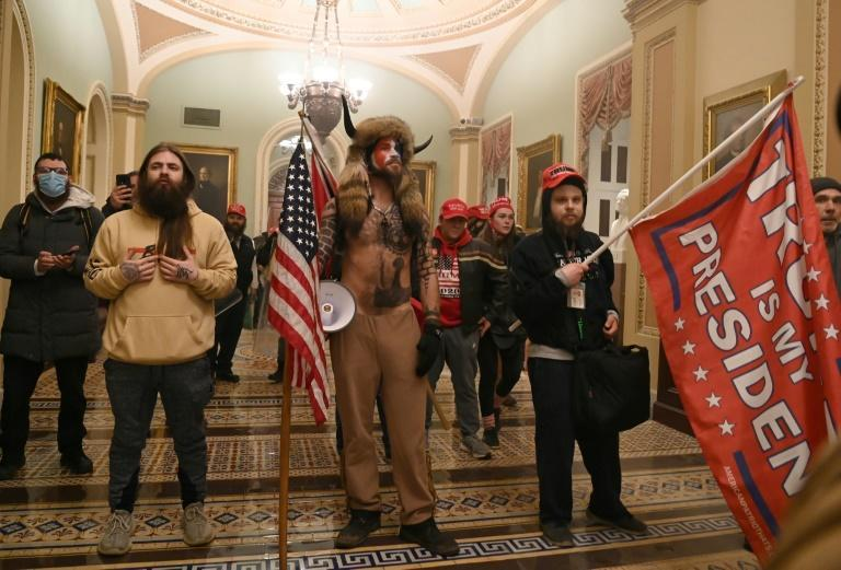 Supporters of US President Donald Trump, including member of the QAnon conspiracy group Jacob Anthony Chansley (C), enter the US Capitol