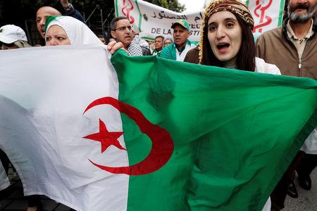 Doctors carry a national flag as they march during a protest calling on President Abdelaziz Bouteflika to quit, in Algiers, Algeria March 19, 2019. REUTERS/Zohra Bensemra