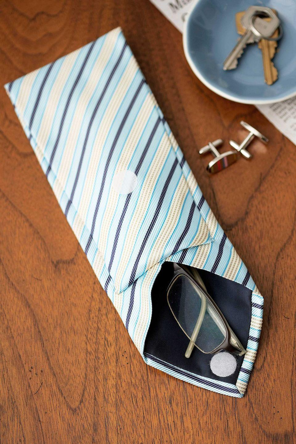 <p>Transform a traditional necktie into a nifty eyeglass case. </p><p><strong>Step 1: </strong>Lay a tie front side down. Measure and mark 17 inches in from the pointed tip, then cut the tie widthwise. Discard the narrow end of the tie.</p><p><strong>Step 2: </strong>Using a seam ripper, open the seam along the back of the tie at least six inches, to create a pouch for the glasses.</p><p><strong>Step 3: </strong>Measure eight inches in from the cut end and mark. Fold the tie at the mark toward the pointed tip; tuck under 1/2 inch of cut edge and pin.</p><p><strong>Step 4</strong>: Using hand-stitches along the top and sides, secure the folded-over portion of tie to the top layer of fabric beneath it (taking care not to sew the pouch closed). Finish by affixing a set of self-adhesive Velcro dots to keep the case closed.</p>