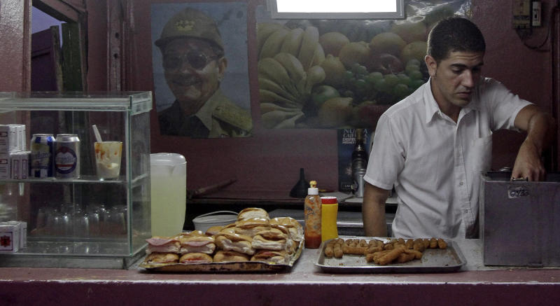 **CAPTION CORRECTS FOOD BOOTH TO STATE-OWNED ** - A worker prepares food for the day's customers at a state-owned food booth that has a poster of Cuba's President Raul Castro taped to the wall, in Havana, Cuba, Friday June 3, 2011. Castro celebrates his 80th birthday Friday. There has been no word of any plan to honor the Cuban president publicly. (AP Photo/Franklin Reyes)