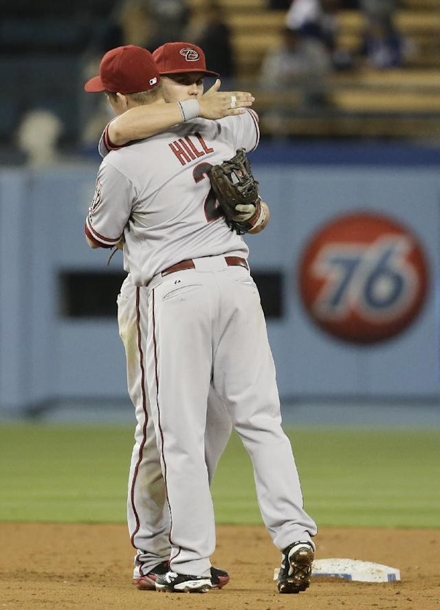 Arizona Diamondbacks second baseman Aaron Hill, left, and Chris Owings hug after their 12th inning win a baseball game against the Los Angeles Dodgers in Los Angeles, Friday, April 18, 2014. (AP Photo/Chris Carlson)