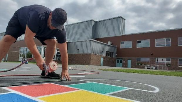 Artist Allie Howe puts the finishing touches on his 3D hopscotch painting on the grounds of King Street Elementary School. (Shane Fowler/CBC News - image credit)