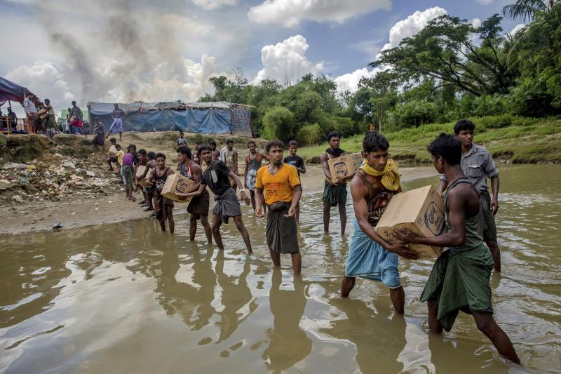 In this Sept. 15, 2017 file photo, Rohingya Muslims carry food items across from Bangladesh towards no man's land where they have set up a refugee camp, as smoke rise from fire across the border in Myanmar, in Tombru. Some 6,000 Rohingya Muslim refugees who fled attacks in Myanmar last year live at the cloudiest edges of the border with Bangladesh, in a no man's land that seems to be neither Myanmar nor Bangladesh. Many stay in these places because they are from nearby villages, and can see the wreckage of their former homes. But the Myanmar government insists no man's land doesn't exist, and the 6,000 refugees are living inside Myanmar. (AP Photo/Dar Yasin, File)