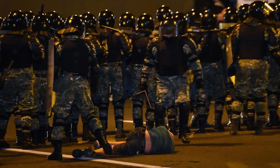 A man lies on the ground in front of riot police during a protest in Minsk on Sunday.