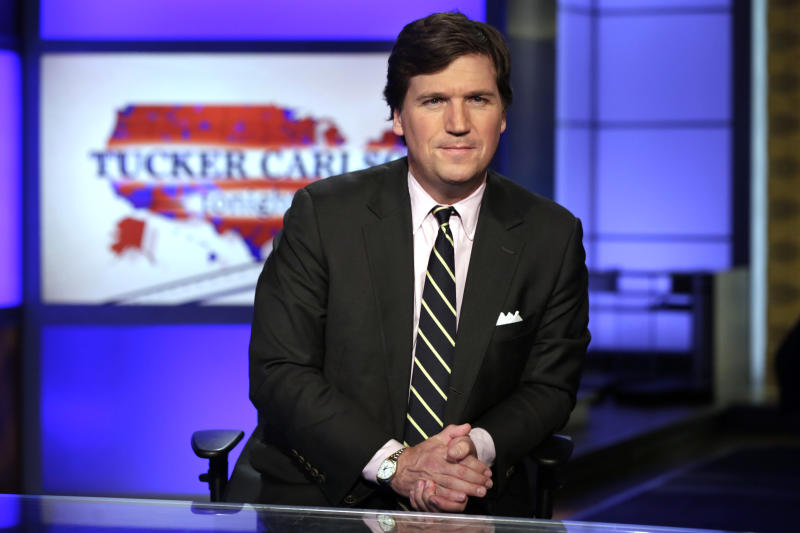 "FILE - In this March 2, 2017 file photo, Tucker Carlson, host of ""Tucker Carlson Tonight,"" poses for photos in a Fox News Channel studio, in New York. The Fox News host and longtime conservative commentator has a two-book deal with Threshold Editions, the publisher said Tuesday, May 2.  Carlson also authored, ""Politicians, Partisans, and Parasites: My Adventures in Cable News,"" which came out in 2003. (AP Photo/Richard Drew, File)"