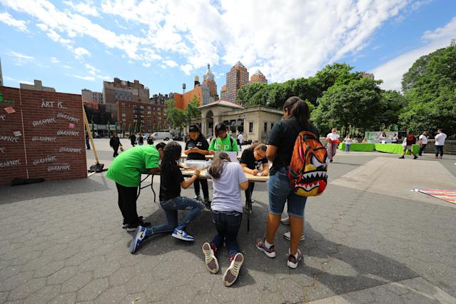 <p>Students from I.S. 117 Joseph H. Wade in the Bronx create art on one of the tables in Union Square Park in New York City on June 5, 2018. (Photo: Gordon Donovan/Yahoo News) </p>