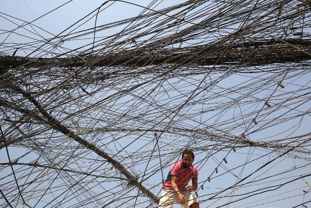 An Iraqi man checks electrical cables in Baghdad, where anti-corruption campaigners say $40 billion invested in Iraq's power grid has been skimmed off (AFP Photo/AHMAD AL-RUBAYE)