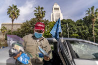 Uber driver Jose Luis Guevara, a member of the Mobile Workers Alliance, shows personal protective equipment, PPE supplies he provides freely to ride sharing customers for their safety, outside Los Angeles City Hall Tuesday, Jan. 12, 2021. Drivers for app-based ride-hailing and delivery services are suing to overturn a California ballot initiative that makes them independent contractors instead of employees eligible for benefits and job protections. The lawsuit filed Tuesday, Jan. 12, 2021 in the California Supreme Court said Proposition 22 is unconstitutional because it limits the power of the Legislature to grant workers the right to organize and excludes drivers from being eligible for workers' compensation. (AP Photo/Damian Dovarganes)