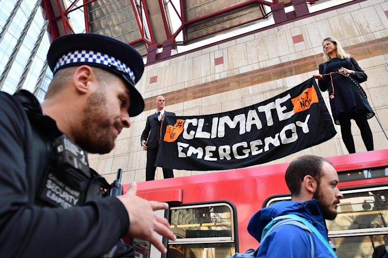 Climate change protesters stand atop a DLR train at Canary Wharf (AFP/Getty Images)