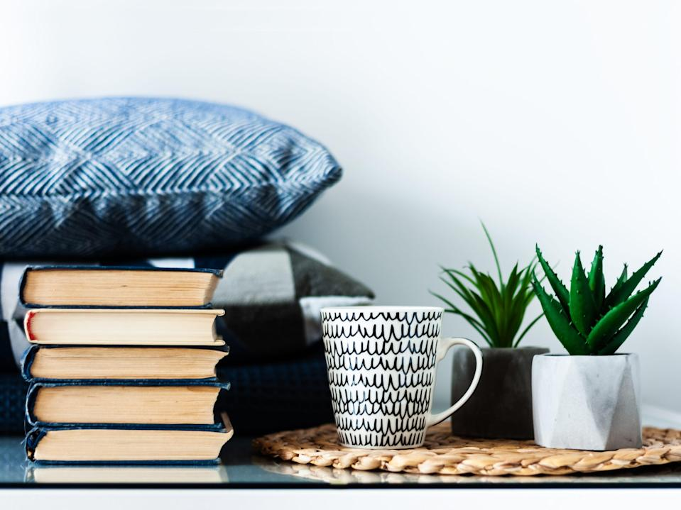 Cozy home interior decor: white and black cup, stack of books, plants in pots on a wicker